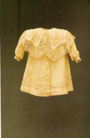 Vestido infantil de fustão branco forado, mangas curtas, pala, mangas e barra com passamanaria, sutache e rendas.Fecha-se por meio de dois botõtes e dois colchetes de gancho - Década de 1920